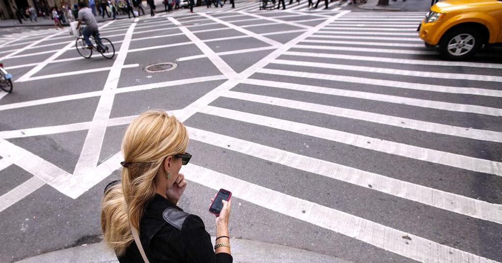 pedestres no trânsito usando celular